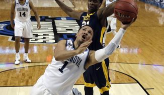Villanova's Jalen Brunson, front, drives past West Virginia's Wesley Harris during the first half of an NCAA men's college basketball tournament regional semifinal Friday, March 23, 2018, in Boston. (AP Photo/Charles Krupa)