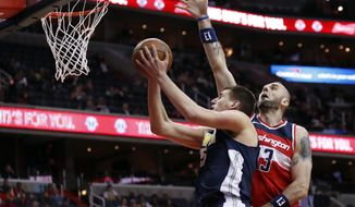 Denver Nuggets center Nikola Jokic (15), from Serbia, shoots past Washington Wizards center Marcin Gortat (13), from Poland, during the first half of an NBA basketball game, Friday, March 23, 2018, in Washington. (AP Photo/Alex Brandon)