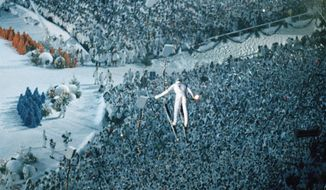 FILE - In this Feb.12,1994, file photo, ski jumper Stein Gruben soars over the crowd as he carries the Olympic Torch during opening ceremonies for the 1994 Lillehammer Olympics in Lillehammer, Norway. The Norwegian ski resort of Lillehammer, widely regarded as the most popular Winter Olympics, may bid again. (AP Photo/Michael Euler, File)