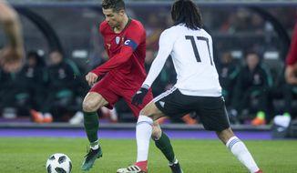 Portugal's Cristiano Ronaldo, left, in action against Egypt's Mohamed Elneny, right, during their soccer friendly game Portugal against Egypt, in the Letzigrund stadium in Zurich, Switzerland, on Friday, March 23, 2018. (Melanie Duchene/Keystone via AP)