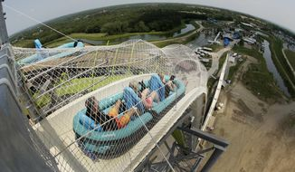 """FILE - In this July 9, 2014, file photo, riders go down the water slide called """"Verruckt"""" at Schlitterbahn Waterpark in Kansas City, Kan. A former executive with the Kansas water park where a 10-year-old boy died on the giant waterslide has been charged with involuntary manslaughter. Tyler Austin Miles, an operations director for Schlitterbahn, was booked into the Wyandotte County jail Friday, March 23, 2018 and is being held on $50,000 bond. Caleb Schwab died in August 2016 on the 17-story Verruckt water slide at the park in western Kansas City, Kansas. (AP Photo/Charlie Riedel, File)"""