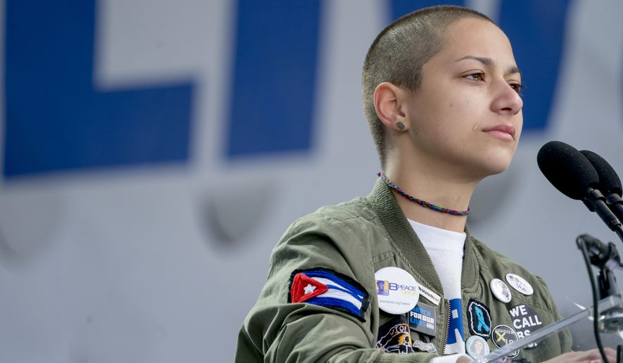 """Emma Gonzalez, a survivor of the mass shooting at Marjory Stoneman Douglas High School in Parkland, Fla., closes her eyes and cries as she stands silently at the podium for the amount of time it took the Parkland shooter to go on his killing spree during the """"March for Our Lives"""" rally in support of gun control in Washington, Saturday, March 24, 2018. (AP Photo/Andrew Harnik)"""