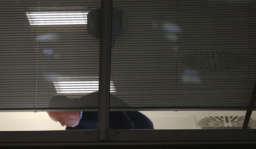 Information Commissioner's Office enforcement officers work inside the offices of Cambridge Analytica in central London after a High Court judge granted a search warrant, Friday March 23, 2018.  The investigation into alleged misuse of personal information continues Friday to determine whether Cambridge Analytica improperly used data from some 50 million Facebook users to target voters with ads and political messages. (Yui Mok/PA via AP)