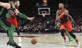 Portland Trail Blazers guard Damian Lillard passes the ball on Boston Celtics center Aron Baynes during the first half of an NBA basketball game in Portland, Ore., Friday, March 23, 2018. (AP Photo/Steve Dykes)