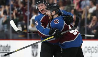 Colorado Avalanche right wing Mikko Rantanen, left, congratulates left wing Gabriel Landeskog after he scored the winning goal against Vegas Golden Knights in the shootout session of an NHL hockey game Saturday, March 24, 2018, in Denver. Colorado won 2-1. (AP Photo/David Zalubowski)