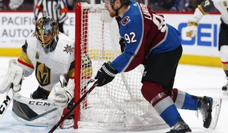 Vegas Golden Knights goaltender Marc-Andre Fleury, left, looks to stop a wraparound shot off the stick of Colorado Avalanche left wing Gabriel Landeskog in the first period of an NHL hockey game Saturday, March 24, 2018, in Denver. (AP Photo/David Zalubowski)