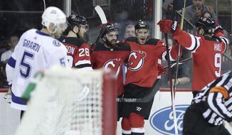 New Jersey Devils players celebrate a goal by right wing Kyle Palmieri, center, as Tampa Bay Lightning defenseman Dan Girardi (5) skates by during the second period of an NHL hockey game, Saturday, March 24, 2018, in Newark, N.J. (AP Photo/Julio Cortez)