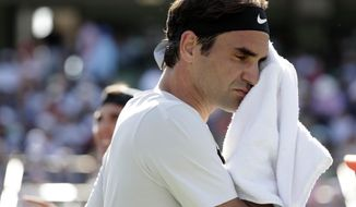 Roger Federer, of Switzerland, wipes his face during his match against Thanasi Kokkinakis, of Australia, at the Miami Open tennis tournament, Saturday, March 24, 2018, in Key Biscayne, Fla. (AP Photo/Lynne Sladky)