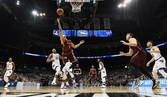 Loyola-Chicago guard Lucas Williamson (1) shoots against Kansas State forward Xavier Sneed (20) during the first half of a regional final NCAA college basketball tournament game, Saturday, March 24, 2018, in Atlanta. (AP Photo/John Amis)