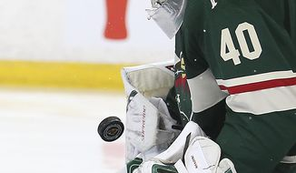 Minnesota Wild's goalie Devan Dubnyk (40) stops the puck from the Nashville Predators' in the second period of an NHL hockey game Saturday, March 24, 2018, in St. Paul, Minn. (AP Photo/Stacy Bengs)