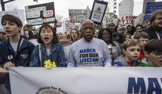 U.S. Rep. John Lewis leads a march of thousands through the streets of Atlanta, Ga., on Saturday, March 24, 2018. Participants in Atlanta and across the nation rallied against gun violence and in support of stricter gun control. (AP Photo/ Ron Harris)