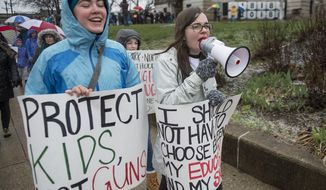 """Baileigh Goodlett, a senior at Bloomington High School South, right, leads the march east on Kirkwood during a local """"March for Our Lives"""" event at the Monroe County Courthouse in Bloomington, Ind. Saturday, March 24, 2018. Summoned to action by student survivors from Marjory Stoneman Douglas High School in Parkland, Fla., hundreds of thousands of teenagers and their supporters rallied in the nation's capital and cities across the U.S. to press for gun control.  (Chris Howell/The Herald-Times via AP)"""