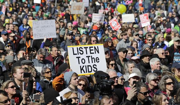 Thousands of protesters look at at a rally following a march in favor of gun control at the Seattle Center Saturday, March 24, 2018, in Seattle. Summoned to action by student survivors of the Florida school shooting, hundreds of thousands of teenagers and their supporters rallied in the nation's capital and cities across America on Saturday to press for gun control in one of the biggest youth protests since the Vietnam era. (AP Photo/Elaine Thompson)