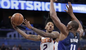 Phoenix Suns' Elfrid Payton (2) passes the ball as he is defended by Orlando Magic's Bismack Biyombo (11) during the second half of an NBA basketball game, Saturday, March 24, 2018, in Orlando, Fla. (AP Photo/John Raoux)