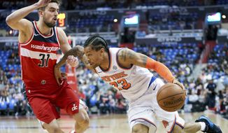 New York Knicks guard Trey Burke (23) drives on Washington Wizards guard Tomas Satoransky (31) in the first half of an NBA basketball game, Sunday, March 25, 2018, in Washington. (AP Photo/Andrew Harnik)