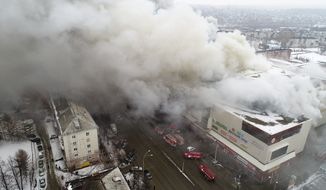 In this Russian Emergency Situations Ministry photo, on Sunday, March 25, 2018, smoke rises above a multistory shopping center in the Siberian city of Kemerovo, about 3,000 kilometers (1,900 miles) east of Moscow, Russia. At least three children and a woman have died in a fire that broke out in a multi-story shopping center in the Siberian city of Kemerovo. (Russian Ministry for Emergency Situations photo via AP)