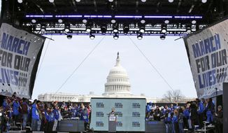 """Emma Gonzalez, a survivor of the mass shooting at Marjory Stoneman Douglas High School in Parkland, Fla., stands silently at the podium for the amount of time it took the Parkland shooter to go on his killing spree during the """"March for Our Lives"""" rally in support of gun control in Washington, Saturday, March 24, 2018. (AP Photo/Alex Brandon)"""