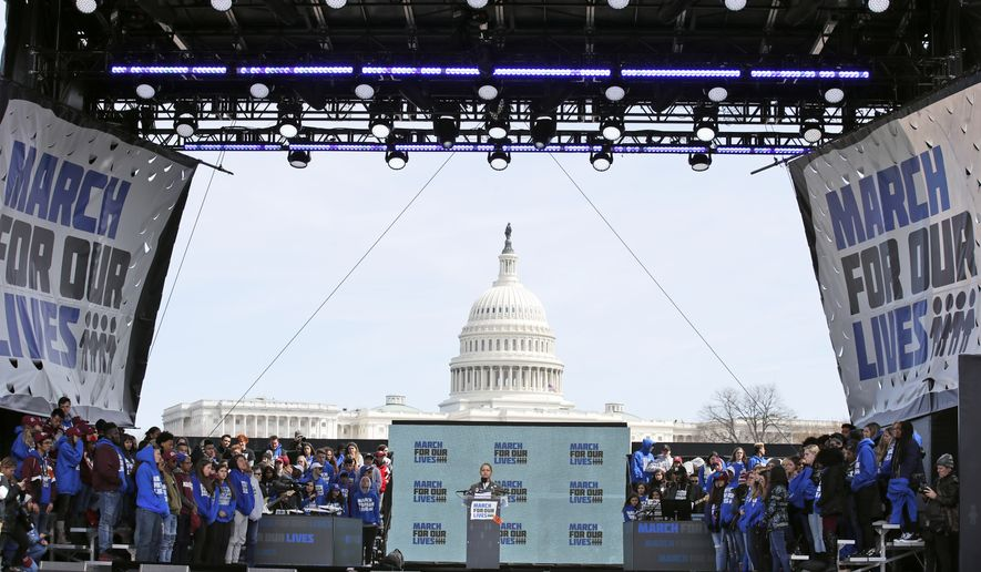 "Emma Gonzalez, a survivor of the mass shooting at Marjory Stoneman Douglas High School in Parkland, Fla., stands silently at the podium for the amount of time it took the Parkland shooter to go on his killing spree during the ""March for Our Lives"" rally in support of gun control in Washington, Saturday, March 24, 2018. (AP Photo/Alex Brandon)"