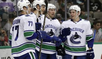 Vancouver Canucks' Nikolay Goldobin (77), Nic Dowd, from second left, Jussi Jokinen, Jussi Jokinen and Troy Stecher, right, celebrate a goal by Dowd in the second period of an NHL hockey game in Dallas, Sunday, March 25, 2018. (AP Photo/Tony Gutierrez)