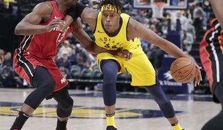 Indiana Pacers center Myles Turner (33) drives on Miami Heat center Bam Adebayo (13) during the second half of an NBA basketball game in Indianapolis, Sunday, March 25, 2018. The Pacers defeated the Heat 113-107 in overtime. (AP Photo/Michael Conroy)