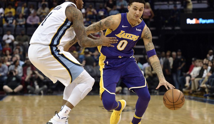 Los Angeles Lakers forward Kyle Kuzma (0) drives against Memphis Grizzlies forward Jarell Martin (1) in the first half of an NBA basketball game Saturday, March 24, 2018, in Memphis, Tenn. (AP Photo/Brandon Dill)
