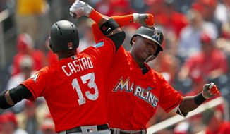 Miami Marlins' Lewis Brinson (9) celebrates with Starlin Castro (13) after hitting a home run in the first inning of a spring training baseball game against the Washington Nationals Tuesday, March 20, 2018, in West Palm Beach, Fla. (AP Photo/John Bazemore)