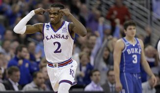 Kansas' Lagerald Vick, left, celebrates after making a 3-point basket as Duke's Grayson Allen is seen in the background during the second half of a regional final game against Duke in the NCAA men's college basketball tournament Sunday, March 25, 2018, in Omaha, Neb. (AP Photo/Nati Harnik) **FILE**