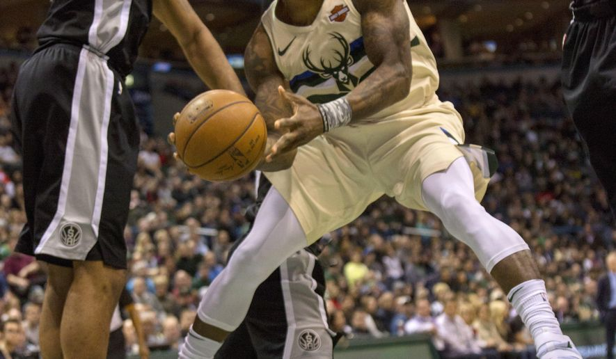 Milwaukee Bucks guard Eric Bledsoe, center, is defended by the San Antonio Spurs during the first half of an NBA basketball game Sunday, March 25, 2018, in Milwaukee. (AP Photo/Darren Hauck)