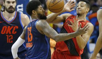 Portland Trail Blazers guard C.J. McCollum, right, loses the ball in front of Oklahoma City Thunder forward Paul George (13) in the first half of an NBA basketball game in Oklahoma City, Sunday, March 25, 2018. Thunder center Steven Adams (12) is at left. (AP Photo/Sue Ogrocki)