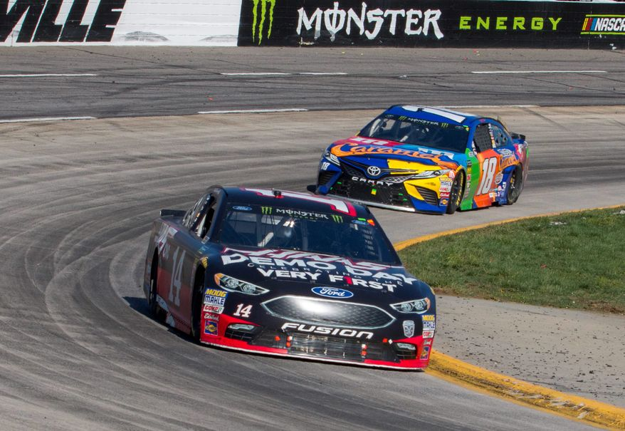 Clint Bowyer passes Kyle Busch en route to winning the NASCAR Cup Series race in Martinsville, Virginia, on Monday. It was Bowyer's first victory since Charlotte in October 2012. (Associated Press)