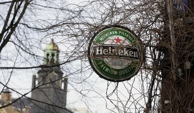 Heineken sign near a cafe in Amsterdam, Netherlands, Friday, Jan. 25, 2008. Brewers Carlsberg and Heineken will buy beermaker Scottish & Newcastle for $15.3 billion, (euro10.4 billion)  the companies said. If the deal goes through, Copenhagen-based Carlsberg A/S would gain sole ownership of Baltic Beverages and S&N's French, Greek and Chinese operations, while Amsterdam-based Heineken NV would take control of its British, American, Indian and other markets. (AP Photo/ Evert Elzinga)