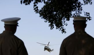 Marines watch as the Marine One helicopter, with President Barack Obama aboard, arrives at Fort McNair, Wednesday, July 4, 2012, in Washington. (AP Photo/Haraz N. Ghanbari)