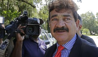 FILE - In this June 15, 2016 file photo, Seddique Mir Mateen, father of Omar Mateen, who died in a gun battle with a SWAT team after he opened fire at the gay nightclub Pulse early Sunday, talks to reporters, across the street of a residence owned by the family, in Fort Pierce, Fla. Seddique Mateen was standing in a crowd behind Democratic presidential nominee, Hillary Clinton, during a campaign event Monday night, Aug. 8, 2016, in Kissimmee, south of Orlando. A campaign official told The Associated Press on Tuesday that he wasn't invited to attend the 3,000-person, open-door public event and that the campaign wasn't aware he was there until it ended. (AP Photo/Alan Diaz, File)