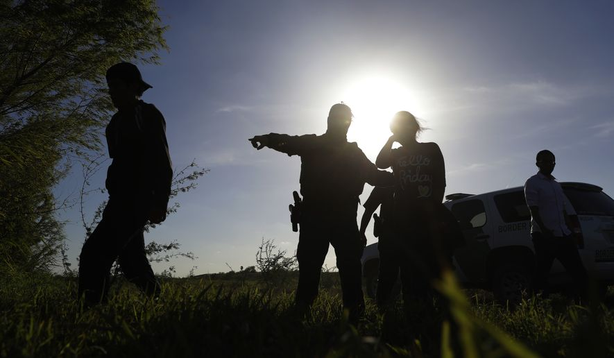 In this Aug. 11, 2017, photo U.S. Customs and Border Patrol agents pick up immigrants suspected of crossing into the United States illegally along the Rio Grande near Granjeno, Texas. The election of President Donald Trump contributed to a dramatic downturn in migration, causing the number of arrests at the border to hit an all-time low in April and helping the U.S. end the 2017 fiscal year at a 45-year low. But since bottoming out in April, the number of immigrants caught at the southern border has been increasing monthly. (AP Photo/Eric Gay)