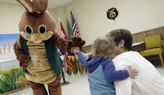In a Saturday, March 24, 2018 photo, Stephanie Smullen of Green Bay helps her 2-year-old son, Willis, give the Easter Bunny a high-five during the Beja Shriners' Breakfast with the Easter Bunny event in Howard, Wis. (Sarah Kloepping/Herald-Times Reporter via AP)