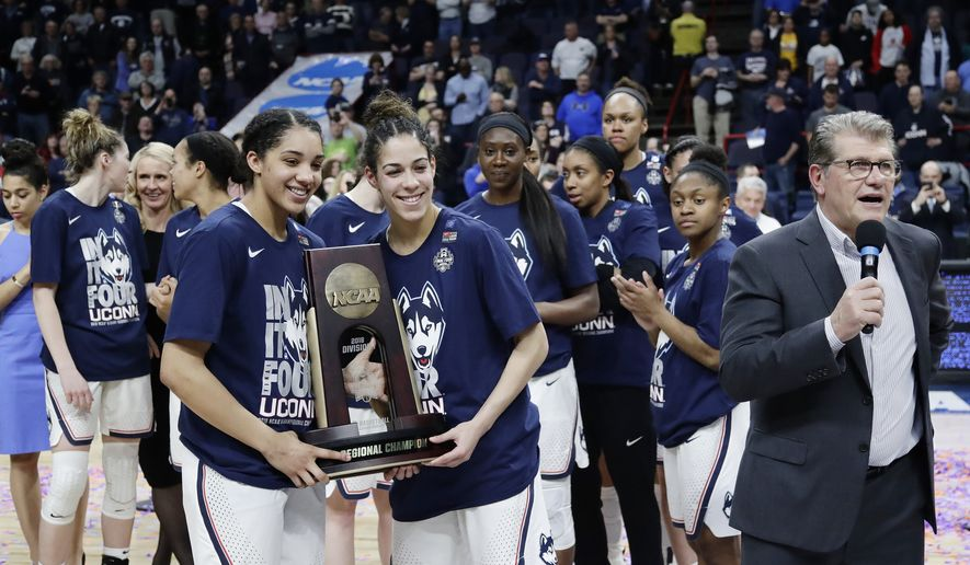 Connecticut's Gabby Williams, left, and Kia Nurse, center, hold the regional championship trophy as head coach Geno Auriemma, right, speaks after a regional final against South Carolina at the women's NCAA college basketball tournament Monday, March 26, 2018, in Albany, N.Y. (AP Photo/Frank Franklin II)