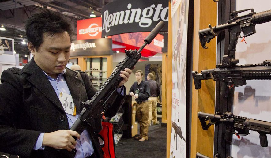 In this Jan. 15, 2013, file photo, accessories manufacturer Kevin Kao, of Irvine, Calif., examines a military grade Remington Adaptive Combat Rifle at the 35th annual SHOT Show in Las Vegas. U.S. gun maker Remington Outdoor Company filed for bankruptcy protection, after years of falling sales and lawsuits tied to the Sandy Hook Elementary School massacre. Records from the bankruptcy court of the district of Delaware show that the company filed late Sunday, March 25, 2018. (AP Photo/Julie Jacobson, File) **FILE**