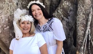 "In this March 24, 2018 photo, brides Karen Cooper, left, and Dana Foglesong pose for a wedding photo in front of their ""groom,"" an ancient ficus tree they've vowed to cherish and protect in Fort Myers, Fla., in hopes of saving it. The tree became the center of a neighborhood controversy when city staff began discussing cutting it down last year. (Amy Bennett Williams/The News-Press via AP)"