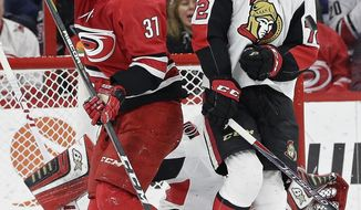 Carolina Hurricanes' Warren Foegele (37) takes a pass as Ottawa Senators' Thomas Chabot (72) defends during the first period of an NHL hockey game in Raleigh, N.C., Monday, March 26, 2018. (AP Photo/Gerry Broome)