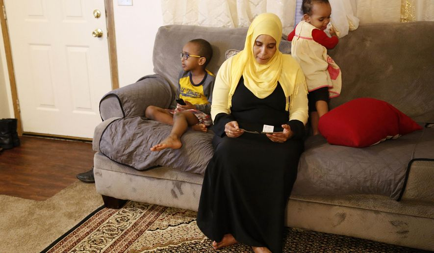 "Amina Olow, a refugee from Somalia, looks at photos of two of her eldest daughters while siting with two of her other children in her Columbus, Ohio, home on Friday, Feb. 23, 2018. The girls, Neemotallah, now 13, and Nastexo, now 10, live in Kenya with other family members. It has been 10 years since their mother has seen them. ""I never thought it would be this long,"" Olow says of her separation from her daughters, who she hopes can join her despite the fact that Somalia is on a list of countries impacted by the Trump administration travel ban. (AP Photo/Martha Irvine)"