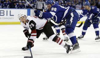 Tampa Bay Lightning defenseman Mikhail Sergachev (98) takes down Arizona Coyotes center Nick Cousins (25) during the first period of an NHL hockey game Monday, March 26, 2018, in Tampa, Fla. (AP Photo/Chris O'Meara)