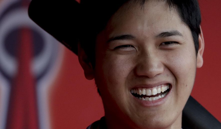 Los Angeles Angels starting pitcher Shohei Ohtani, of Japan, smiles in the dugout before a spring baseball game against the Los Angeles Dodgers in Tempe, Ariz., Wednesday, March 7, 2018. (AP Photo/Chris Carlson)