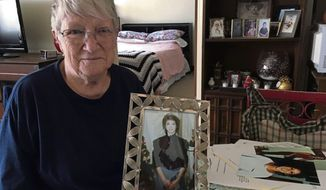 Charlotte Slaugenhoupt poses with a photo of her missing daughter Terri Slaugenhoupt.  In the 27 years that Terri has been missing, there have been virtually no sightings or leads. Her mother hopes that renewed attention will finally answer the question of Terri's whereabouts. (Steven Huba/Pittsburgh Tribune-Review via AP)