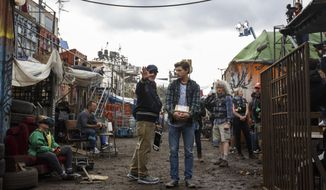 "This cover image released by Warner Bros. Pictures shows director Steven Spielberg, left, and Tye Sheridan on the set of ""Ready Player One."" (Jaap Buitendijk/Warner Bros. Pictures via AP)"