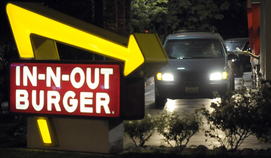 FILE - In this June 8, 2010, file photo, a customer receives an order from the drive-through at an In-N-Out Burger. In-N-Out Burger is seeking a restraining order against an online prankster who posed as the company's CEO at two Los Angeles restaurants, argued with employees and in one instance took a hamburger from a customer, threw it to the ground and stepped on it. (AP Photo/Adam Lau, File)