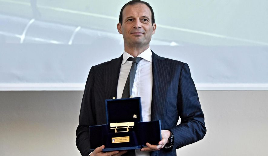 Juventus coach Massimiliano Allegri poses with the golden bench coaching award at the Coverciano's Sports Center, near Florence, Italy, Monday, March 26, 2018. Juventus coach Massimiliano Allegri has won the golden bench coaching award voted by his colleagues for last season. In 2016-17, Allegri guided Juventus to a record sixth straight Serie A title, a third straight Italian Cup championship and the Champions League final. Allegri received 19 votes, Gian Piero Gasperini of Atalanta finished second with 11 votes and Maurizio Sarri of Napoli came third with seven. It's the third time Allegri has won the award. (Maurizio Degl'Innocenti/ANSA via AP)