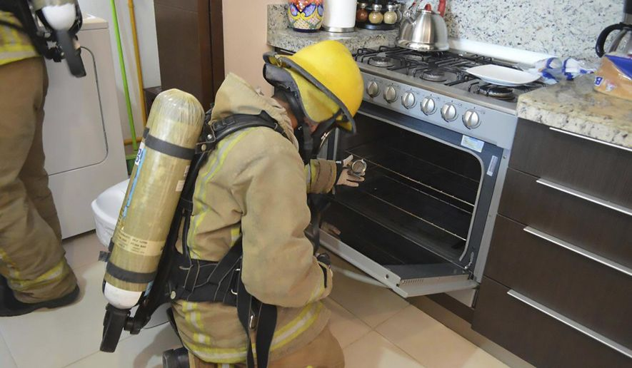 In this undated photo provided by the Quintana Roo Prosecutors Office, a firefighter examines a gas stove in the rented condo where an Iowa couple and their two children died in Tulum, Mexico. Mexican authorities said on Saturday, March 24, 2018 that autopsies indicate the Iowa couple and their two children died from inhaling toxic gas at the rented condo on Mexico's Caribbean coast, but there was no sign of foul play or suicide. (Quintana Roo Prosecutor's Office via AP)