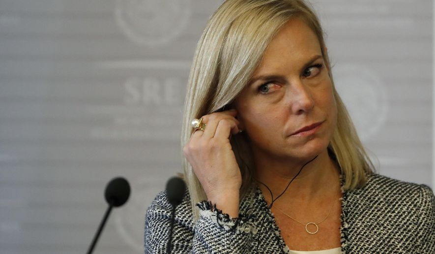 U.S. Secretary of Homeland Security Kirstjen Nielsen places her earpiece for translations before the start of a joint press conference with Mexican Foreign Minister Luis Videgaray in Mexico City, Monday, March 26, 2018. (AP Photo/Eduardo Verdugo)