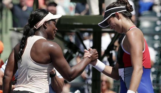 Sloane Stephens, left, shakes hands with Garbine Muguruza, of Spain, after winning their match at the Miami Open tennis tournament, Monday, March 26, 2018, in Key Biscayne, Fla. Stephens won 6-3, 6-4. (AP Photo/Lynne Sladky)