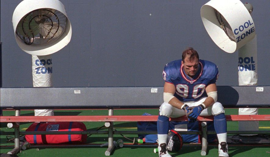 "FILE - In this Sept. 14, 1997, file photo, New York Giants linebacker Corey Widmer sits on the team bench in front of two Cool Zone fans after losing to the Baltimore Ravens, 24-23, at Giants Stadium in East Rutherford, N.J. The Montana Football Hall of Fame inducted eight new members over the weekend, but Widmer declined his nomination saying concussions he suffered while playing football ""destroyed my life."" (AP Photo/Norm Sutaria, file)"